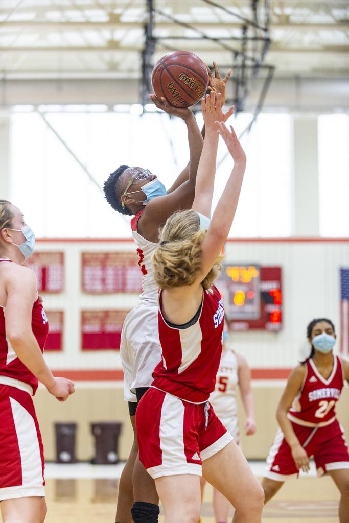 A player drives to the basket as she is being closely defended