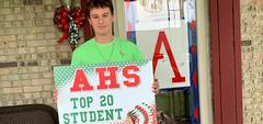 Boy standing on porch holding sign,'AHS Top 20 Student'
