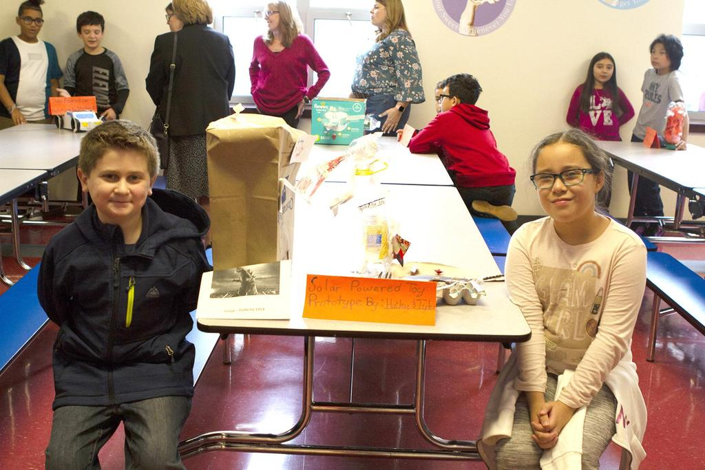 Two students stand next to their STEM projects inside the Webster School cafeteria