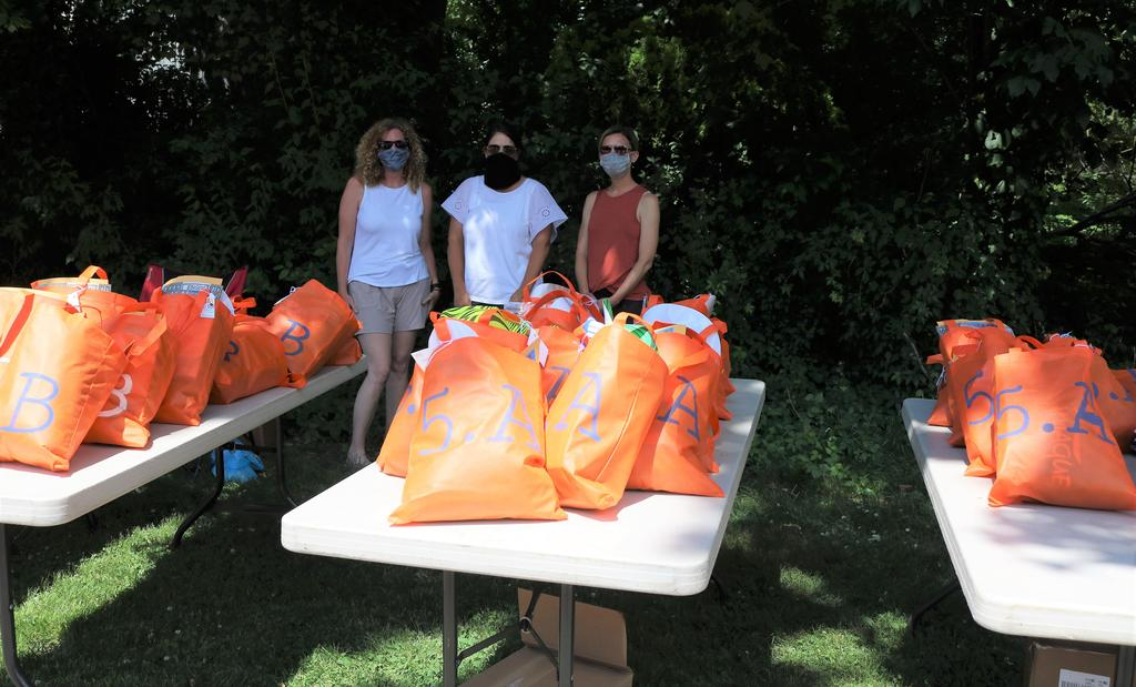 Photo of Tamaques parents behind tables with orange bags for 5th graders during Grade 5 drive by clapout
