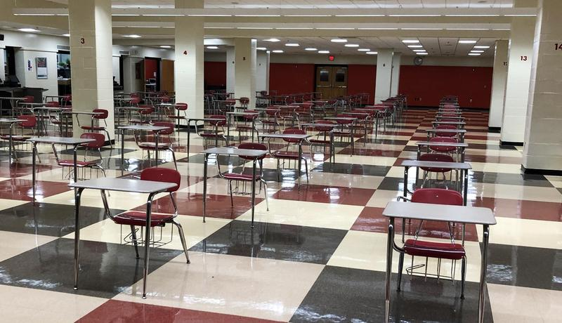 Empty cafeteria with desks spaced six feet apart