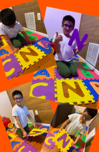 Boy putting together letter floor mat collage