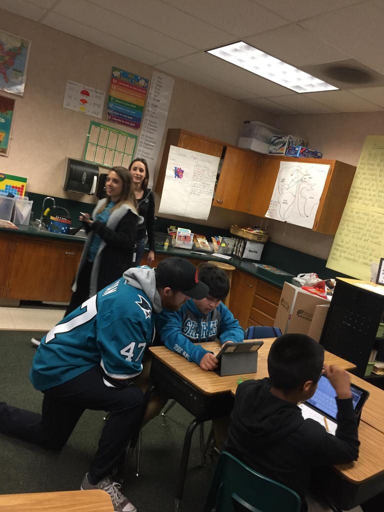 shark player kneels down to look at student's iPad screen
