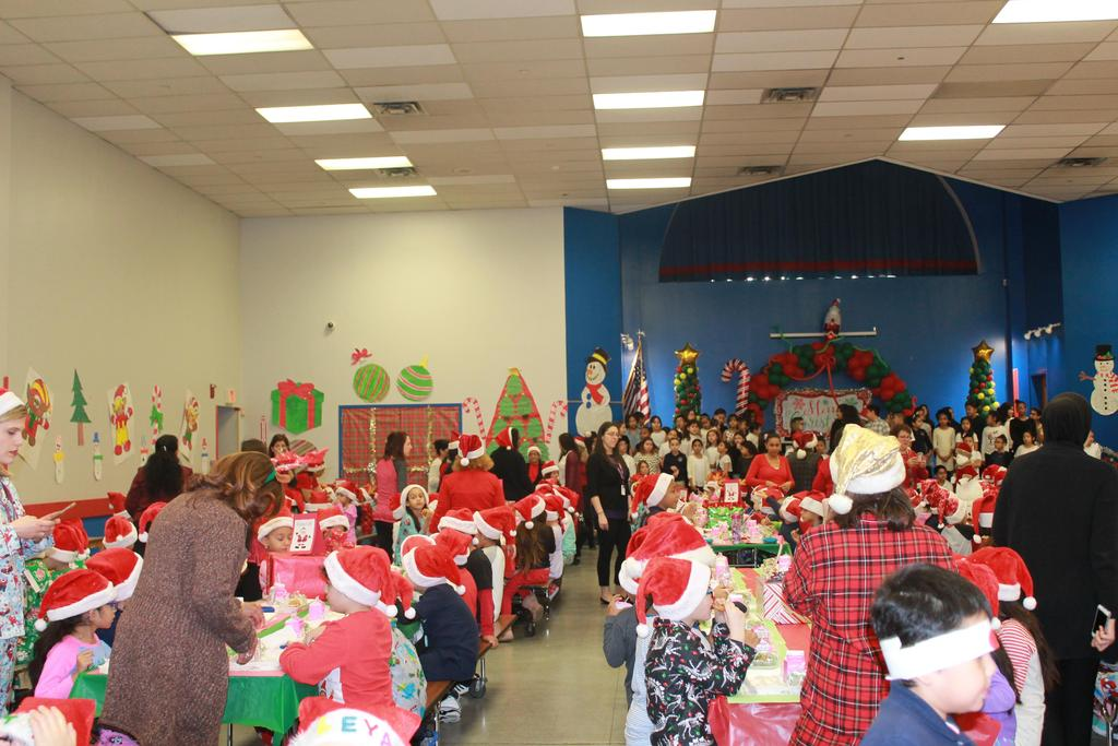 a packed cafeteria with children wearing santa hats in the pj's with adults serving breakfast