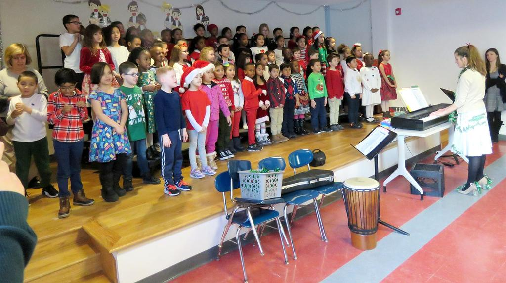 A stage full of students singing, with teacher Rose Whitcomb at the keyboard