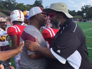 Father and son football coaches hug on the sideline