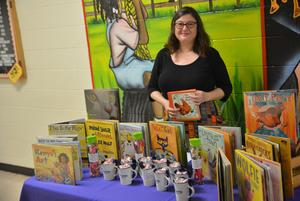 A teacher standing behind a table of displayed books.