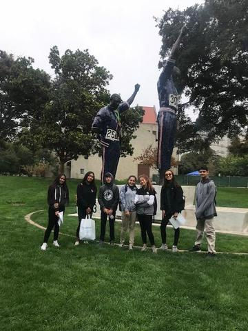 CCA students exploring SJSU's campus and standing by several statues.