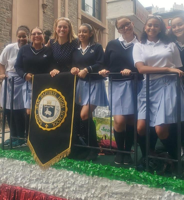 School Pres. in Navy Blue and Girls in White tops blue skirts on parade float