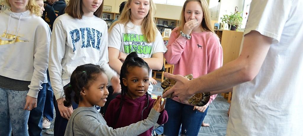 kindergarten and 7th-grade girls meet snake