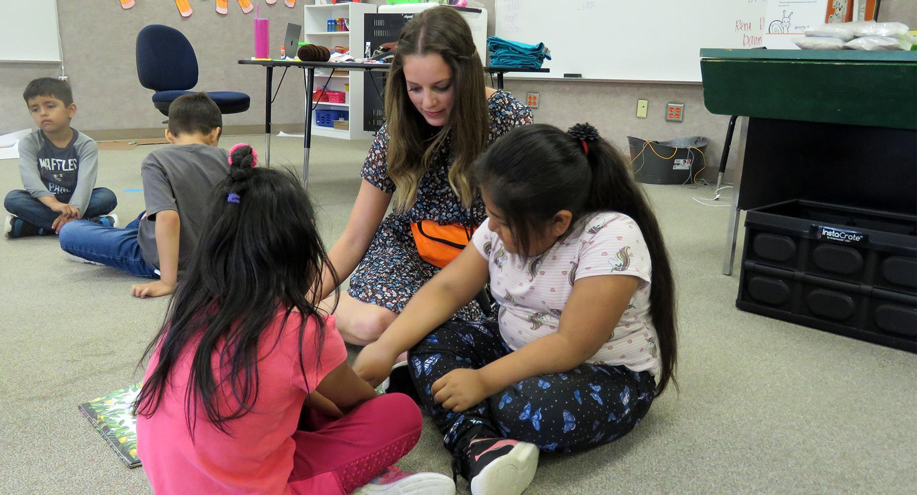 Teacher sits on the floor with two female students as she helps them with a book