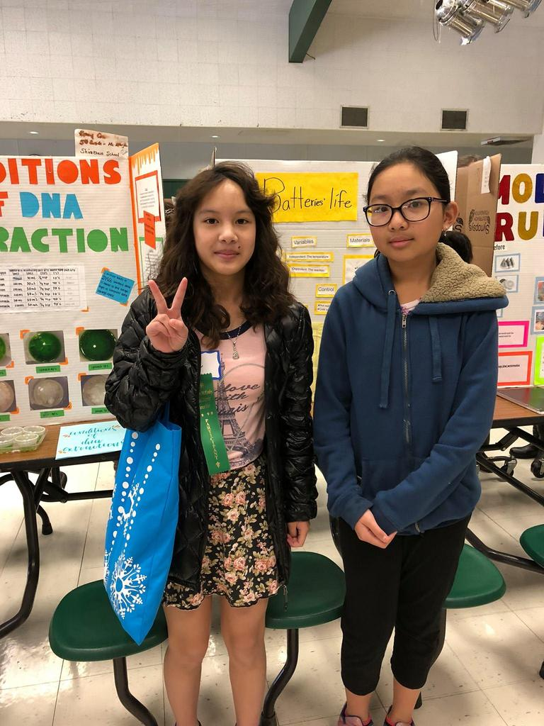 students stand in front of their winning science fair project