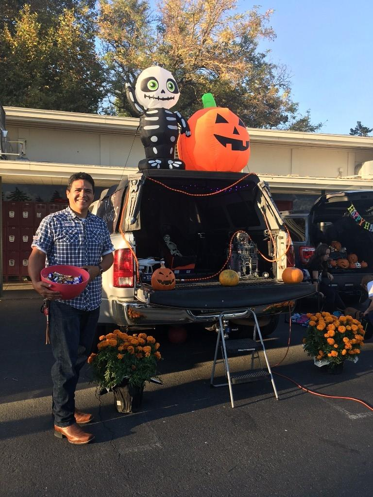 Halloween themed trunk with inflatable pumpkin and skeleton on top