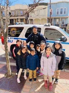UCPD with small children in front of uc vehicle