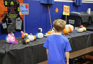 student enjoys viewing creative pumpkins decorated for Wilson School's annual Pumpkin Patch.