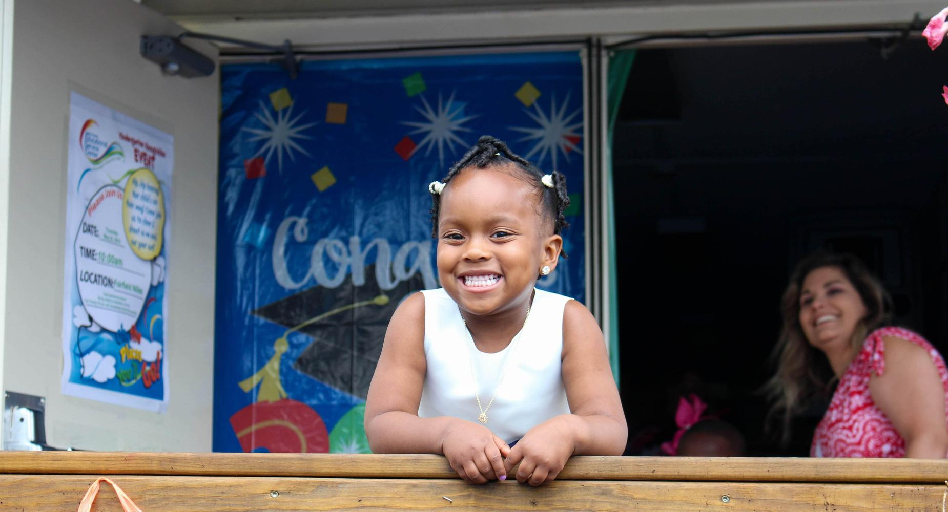 A young Black female Head Start student celebrates her graduation from the program with a smile from the podium