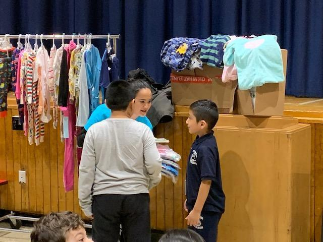 students handing pajamas to adult at assembly