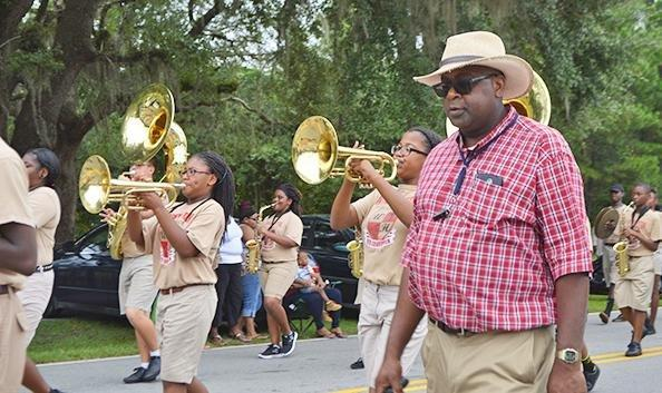 Mr. Manigo marches with band students in a parade