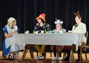 A scene from Alice in Wonderland featuring Alice, the Mad Hatter, Dormouse and the March Hare