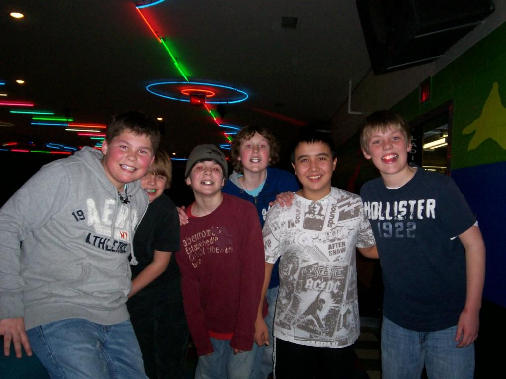 boys smile at camera at dark roller rink