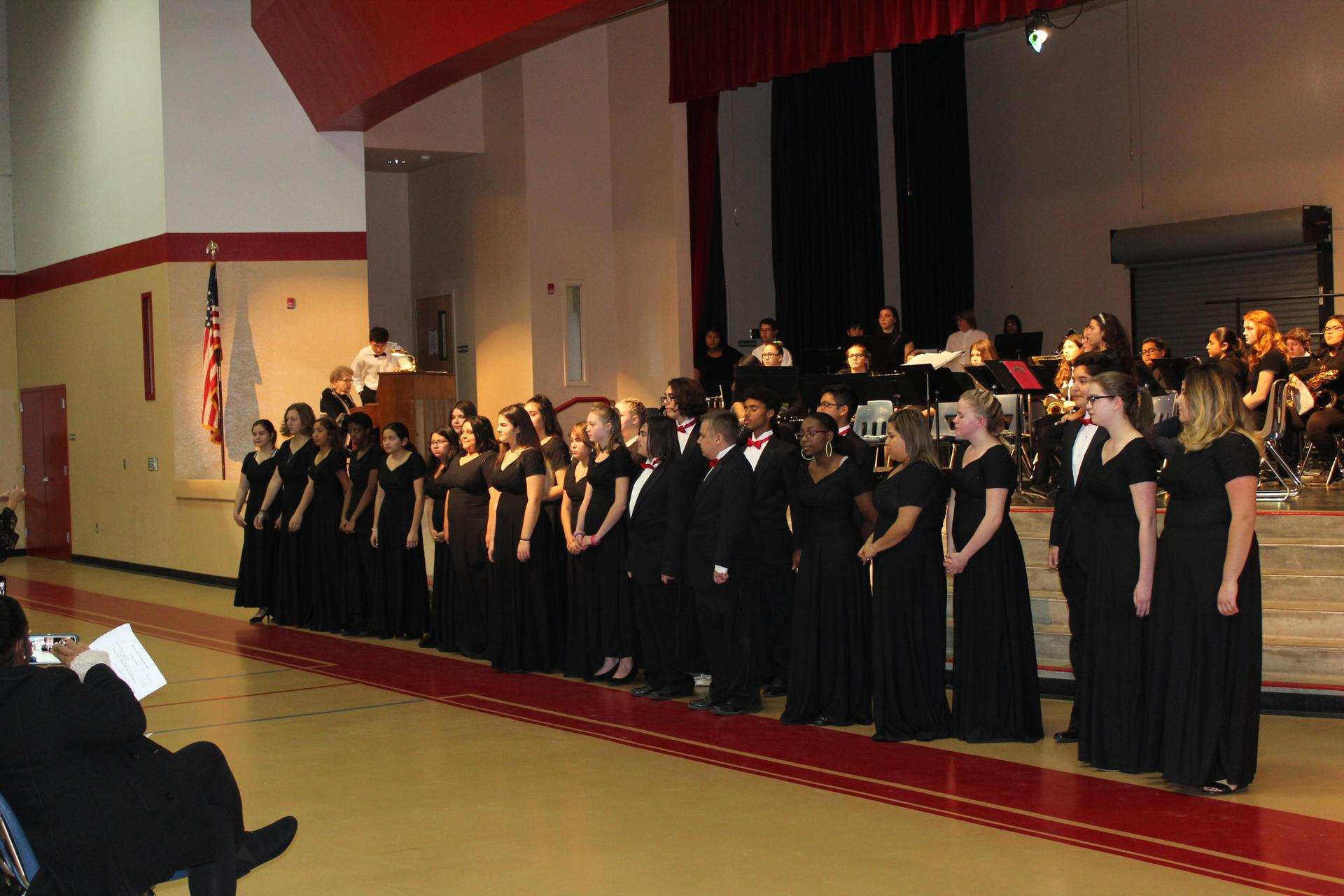 The CUHS Choir stands in front of the stage.