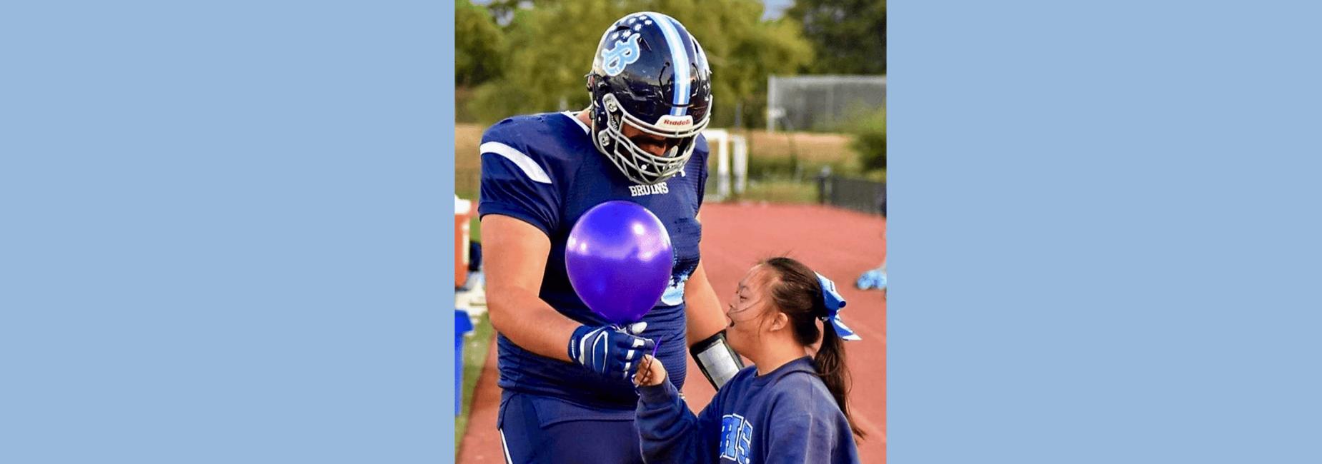 Varsity footballer gives balloon to cheerleader