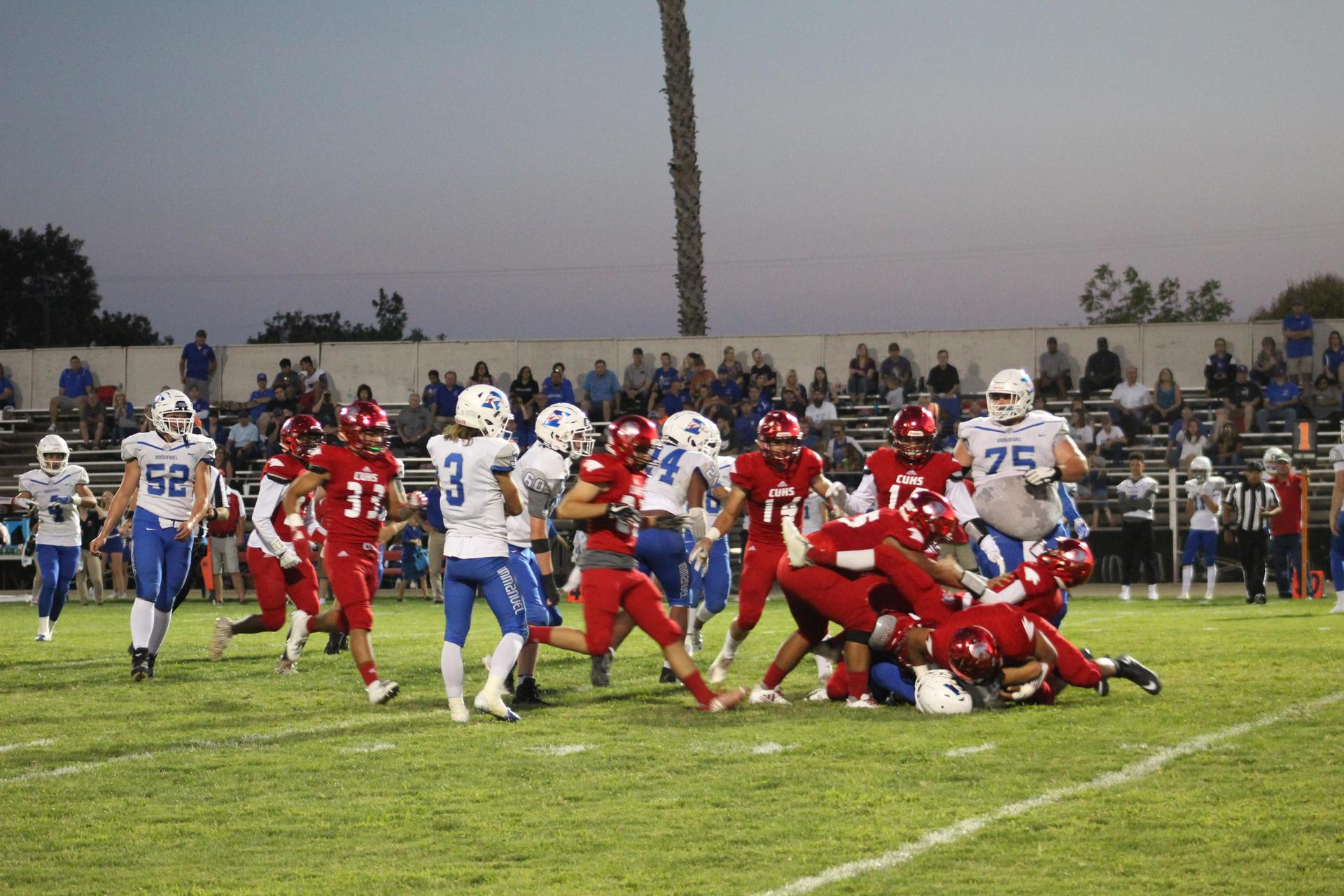 Varsity football players in action vs Immanuel