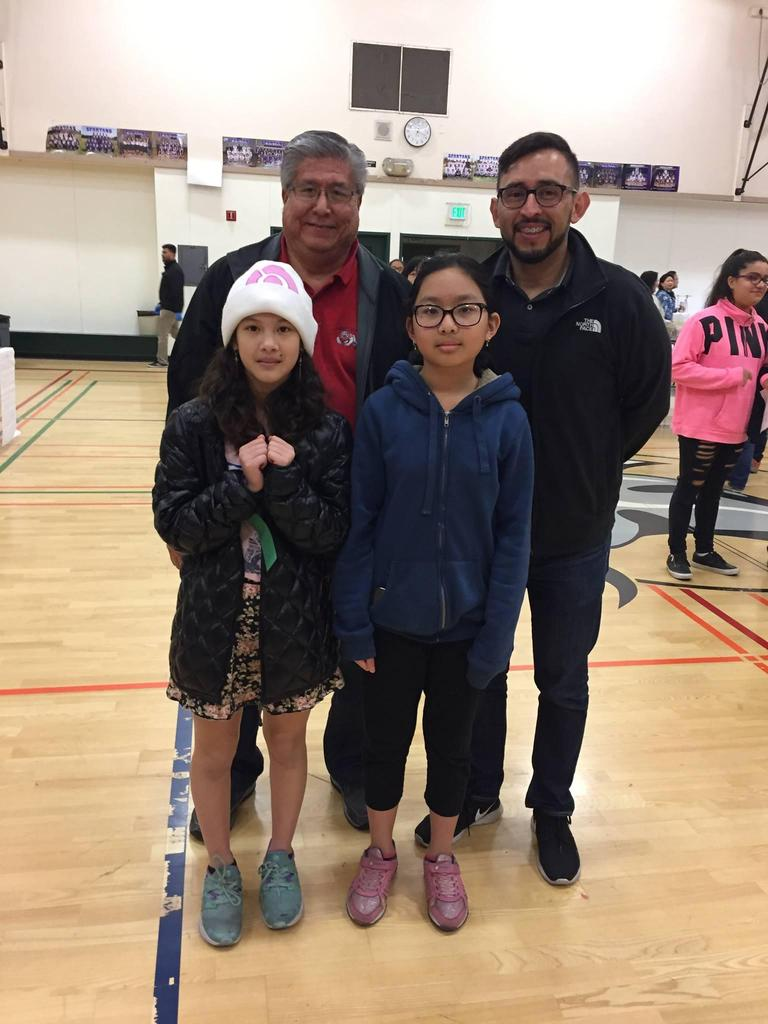 students stand with two FMSD board members at science fair