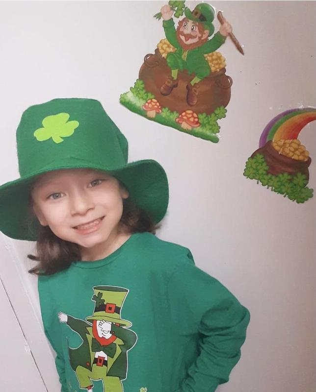 Girl wearing leprechaun shirt and shamrock hat