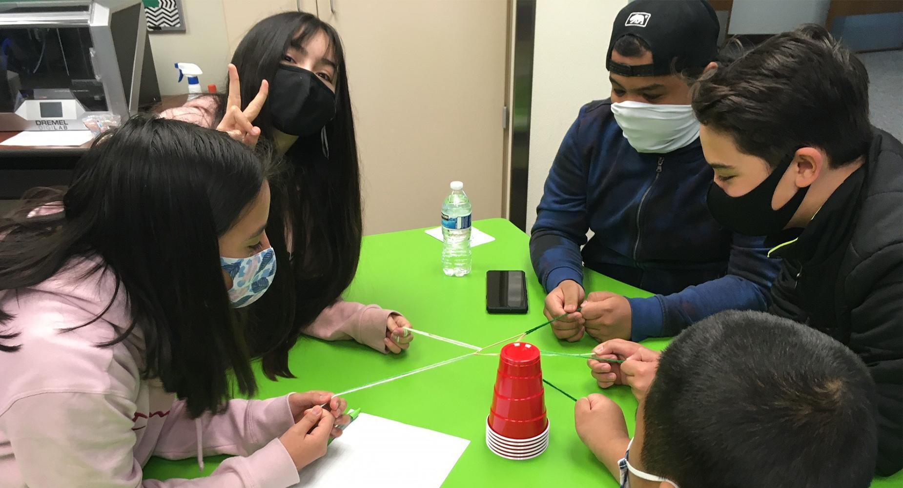 Five middle school students pull on interconnected strings in a team exercise.