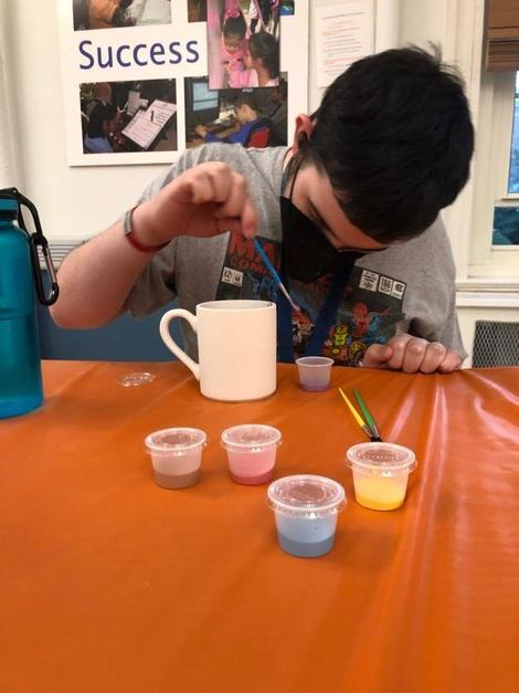 A student is dipping a paint brush into water