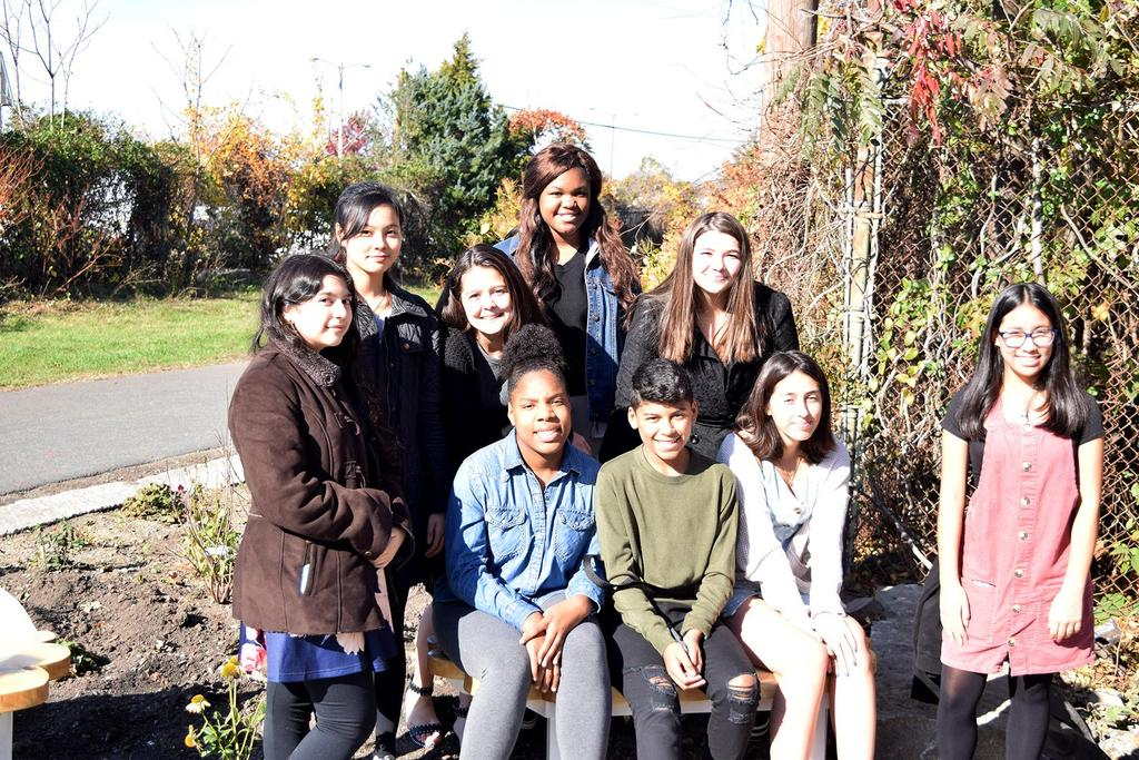 An informal group photo of EPS students inside the rain garden