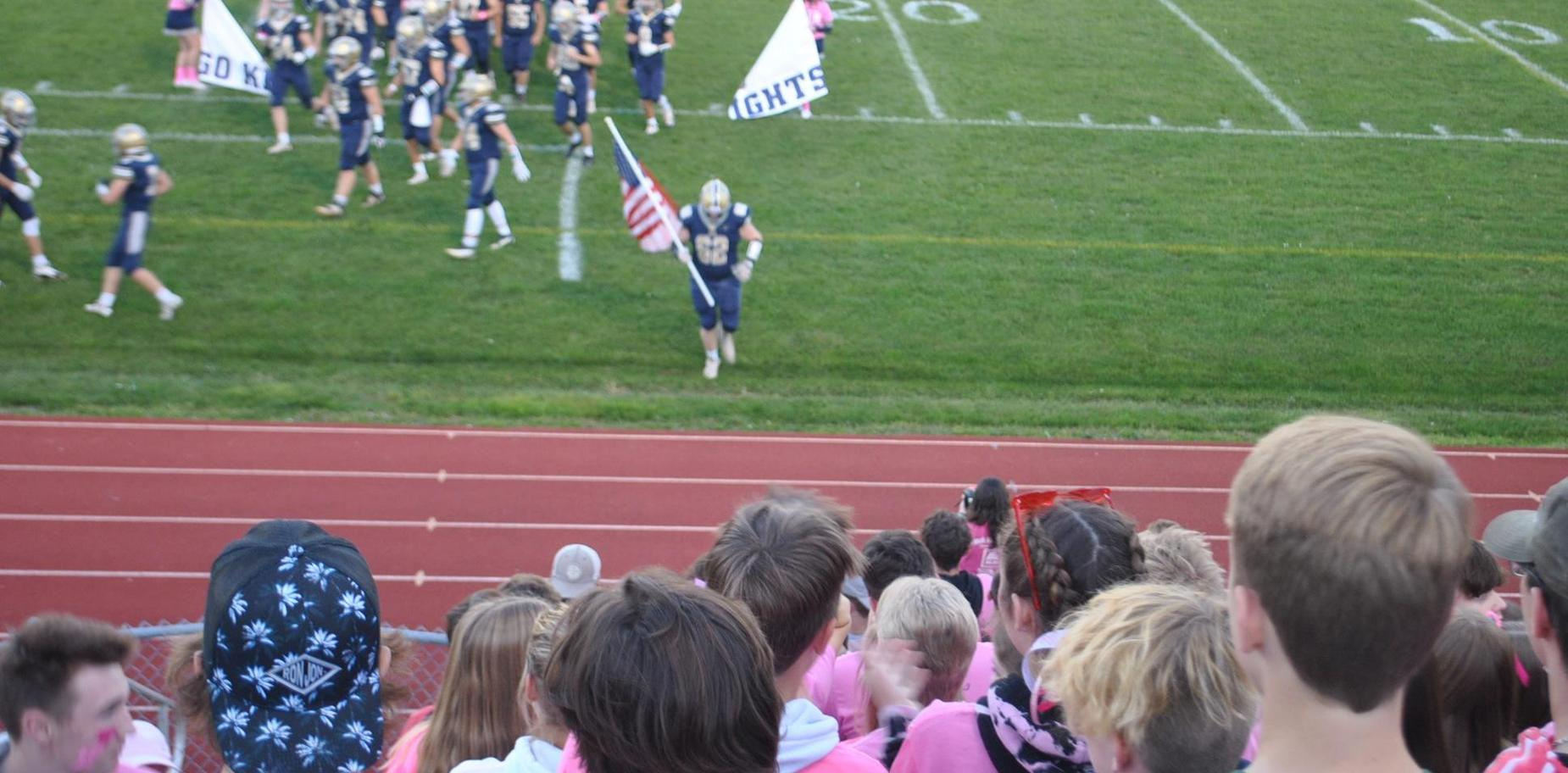 football player bringing flag to student section