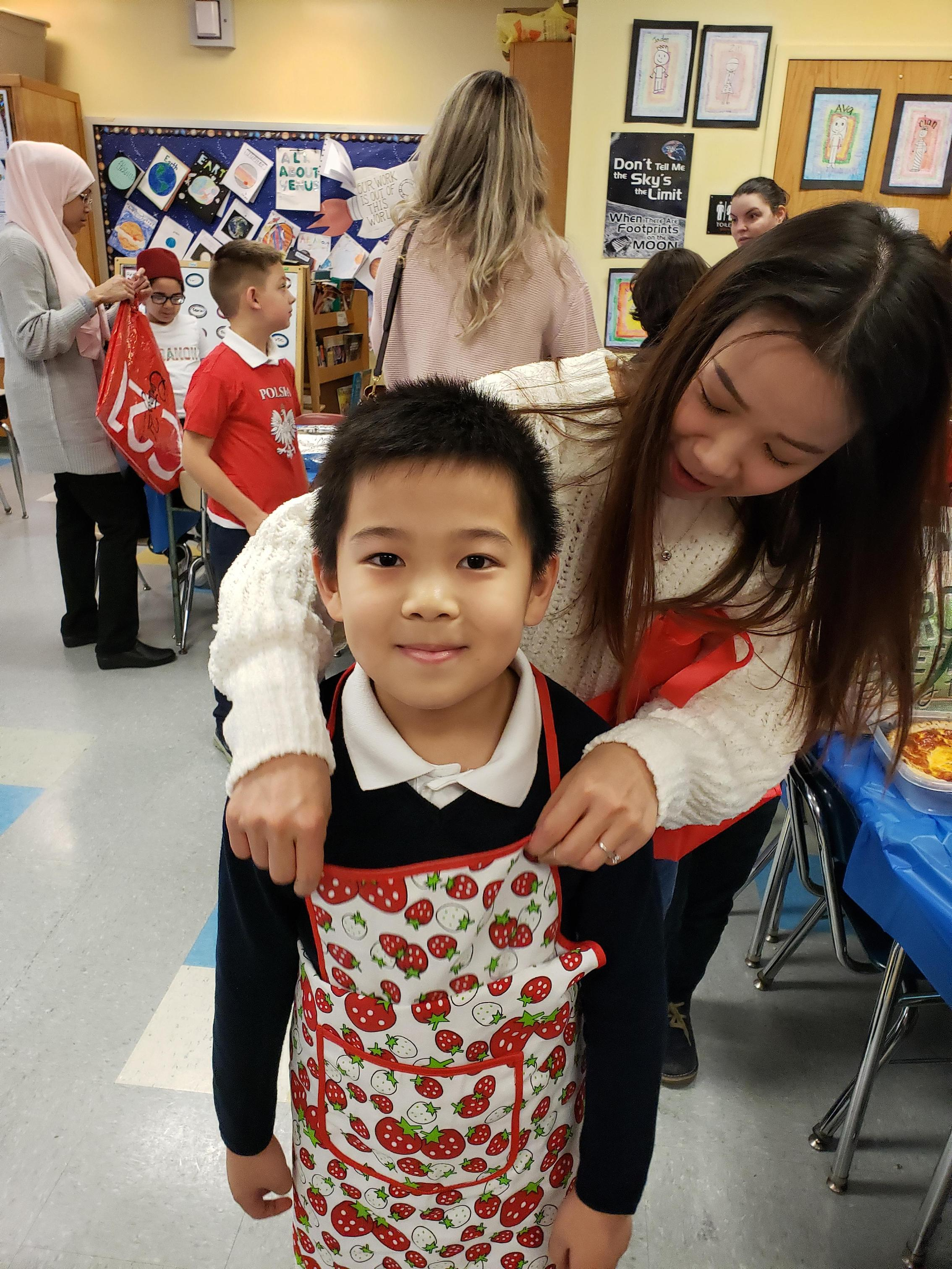 mom placing apron on son
