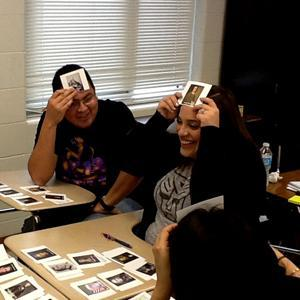 "Two teachers playing a version of the game ""Head's Up""."