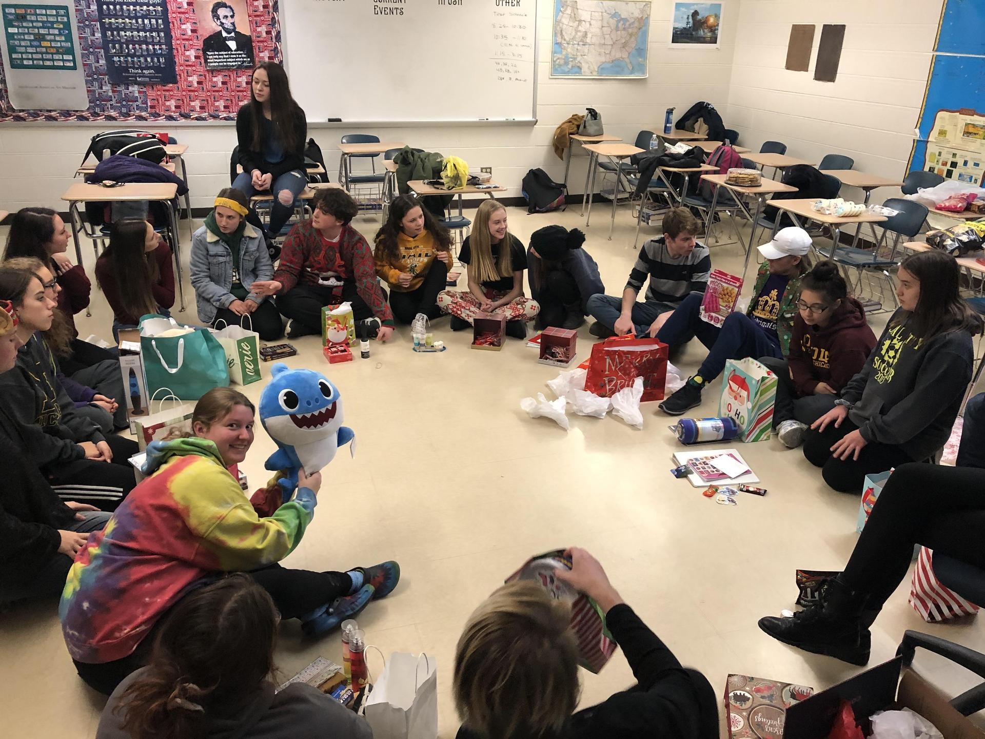 Students in a circle exchanging gifts.