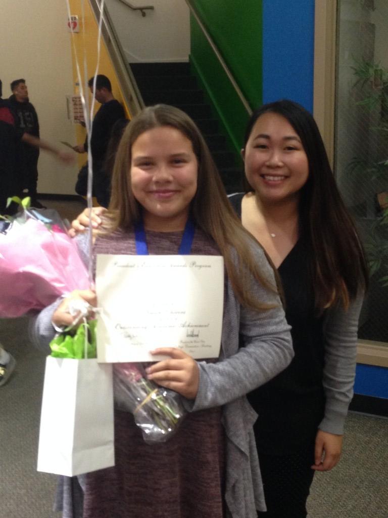 Student holding award.