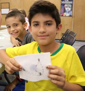 STEM camper sews electrical circuit into fabric to create an E-Textile.