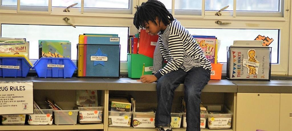Student takes a window seat for book report