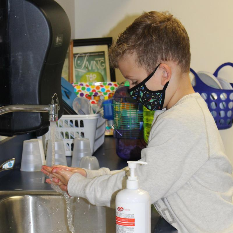 A student washes his hands.