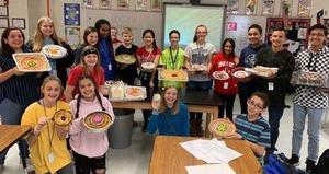 Students holding edible atoms