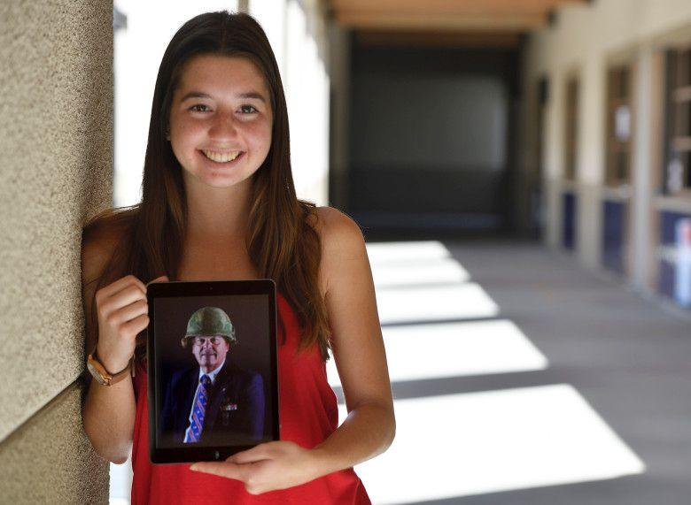 Student posing with a photo of a vietnam veteran