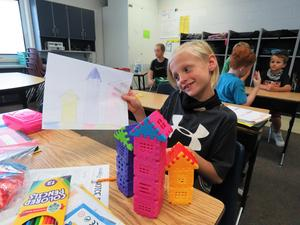 A 4th-grade student builds three towers with MagnaTiles.