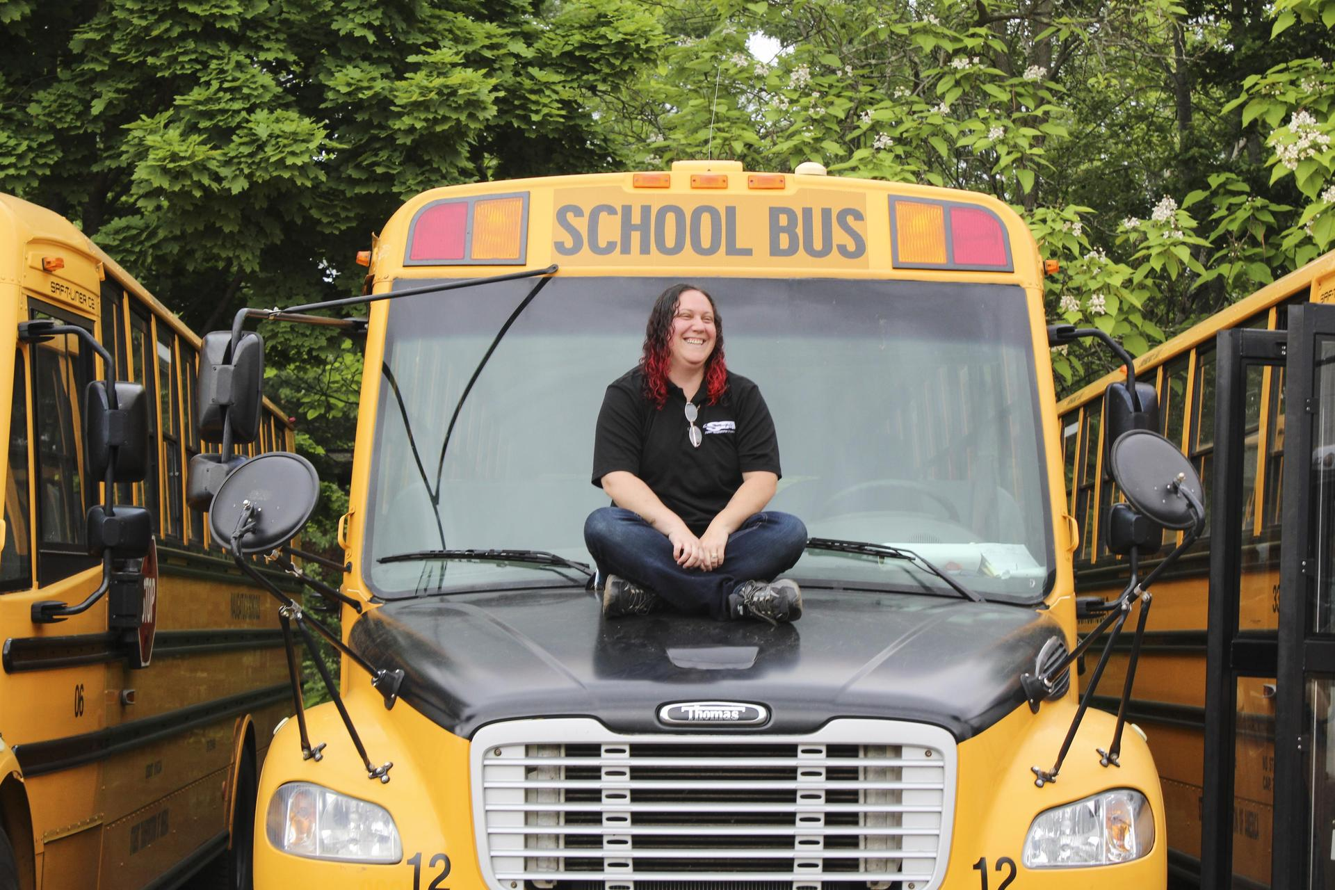 Bus driver sitting on hood of school bus