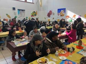 children and adults sitting at tables enjoying the luncheon