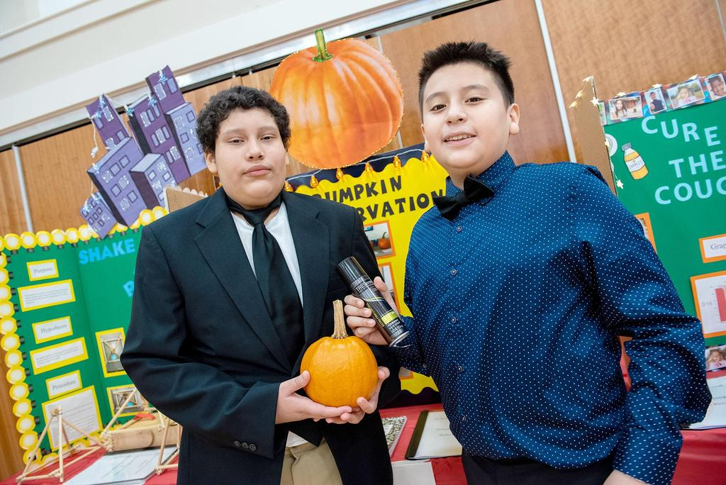 Two students, one holding a small pumpkin, the other an aerosol can