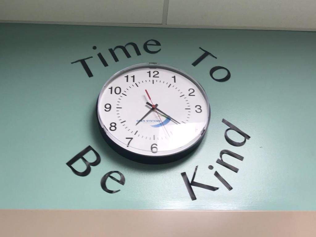 """clock with """"time to be kind"""" decoration"""