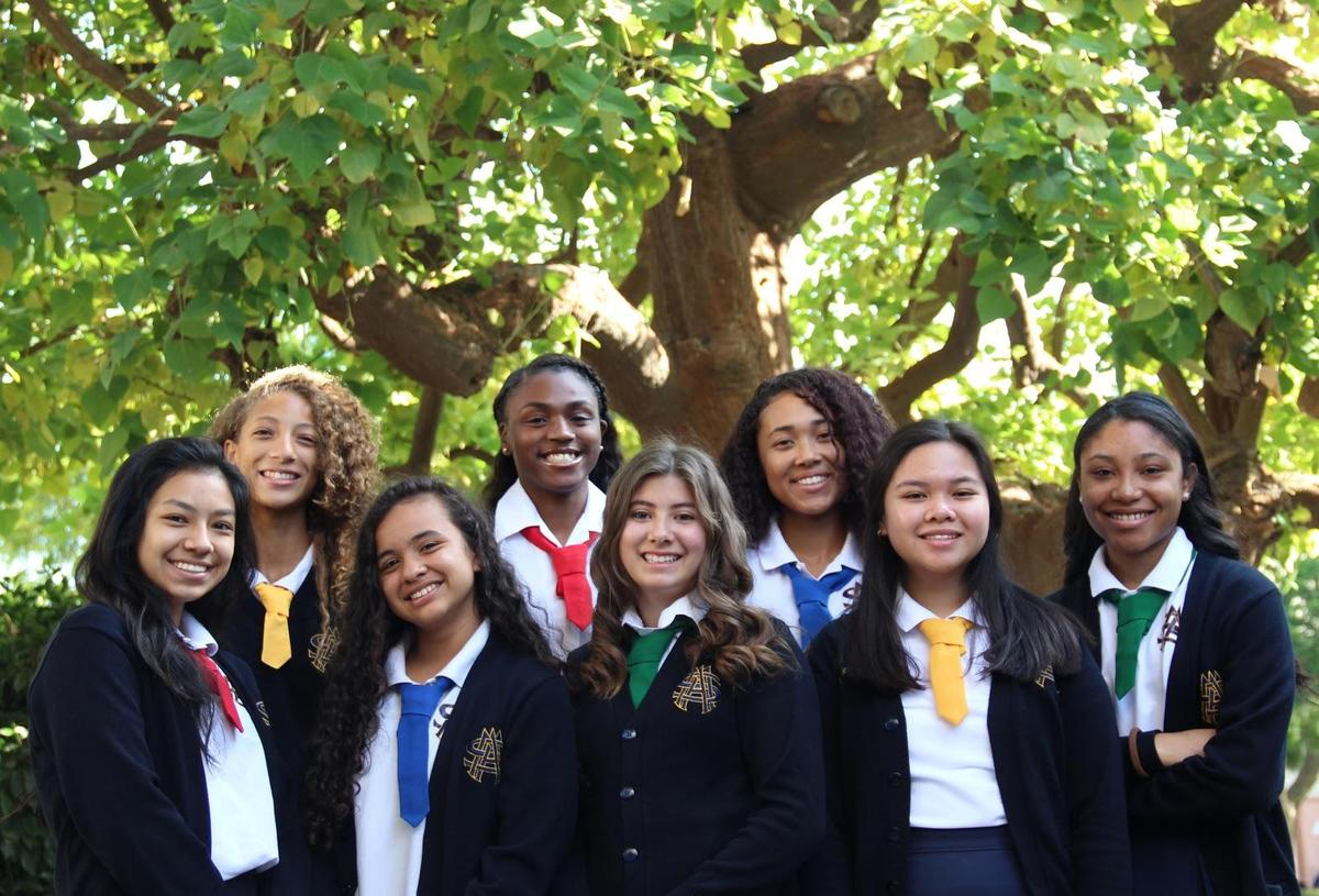 large group of 8 students posing in front of a tree