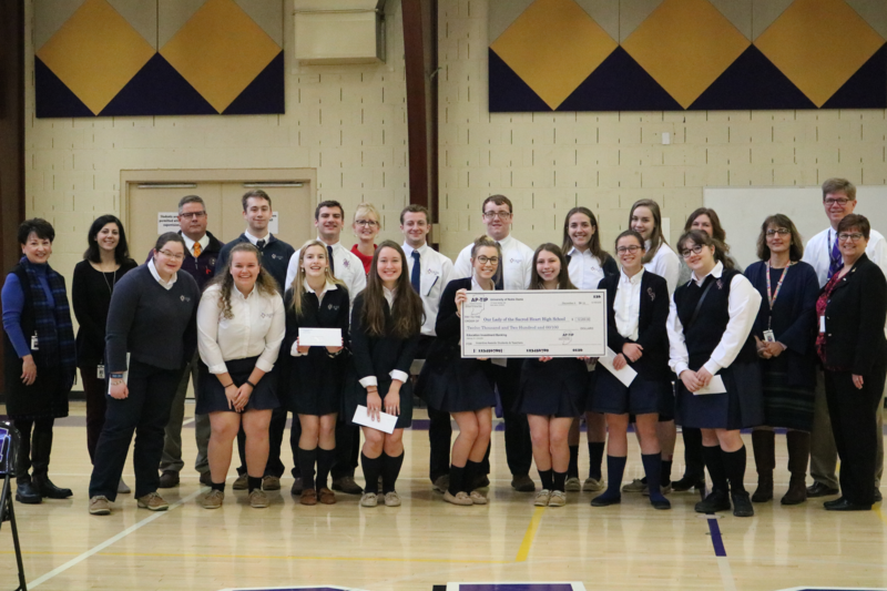 Photo of group of students and teachers receiving a check for the OLSH Notre Dame TIP IN program
