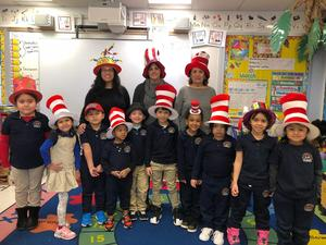 Ms. Sosa and her class wearing Cat in the Hat hats with their aides